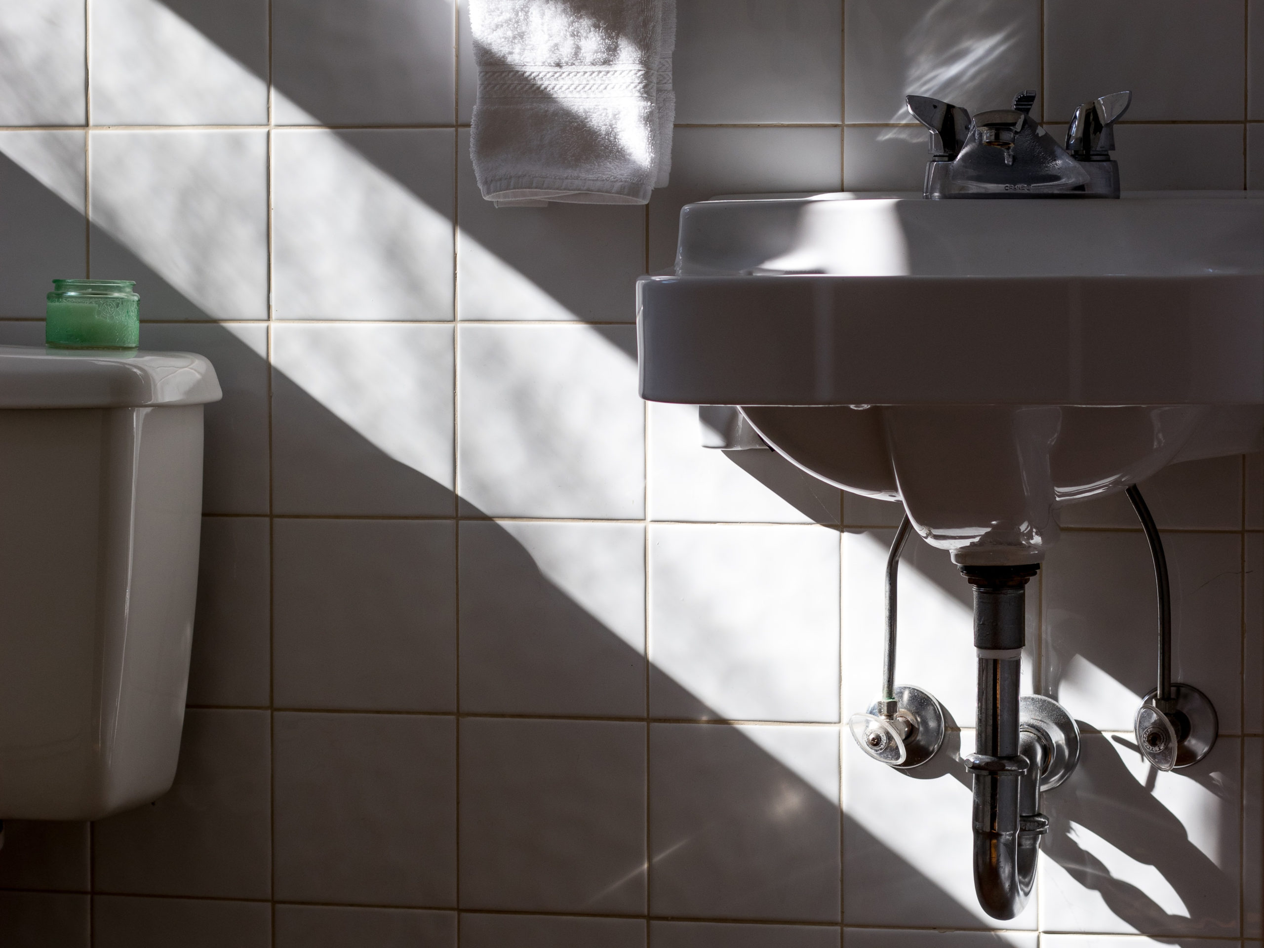 Beautiful bathroom with a shaft of light shining on white tile