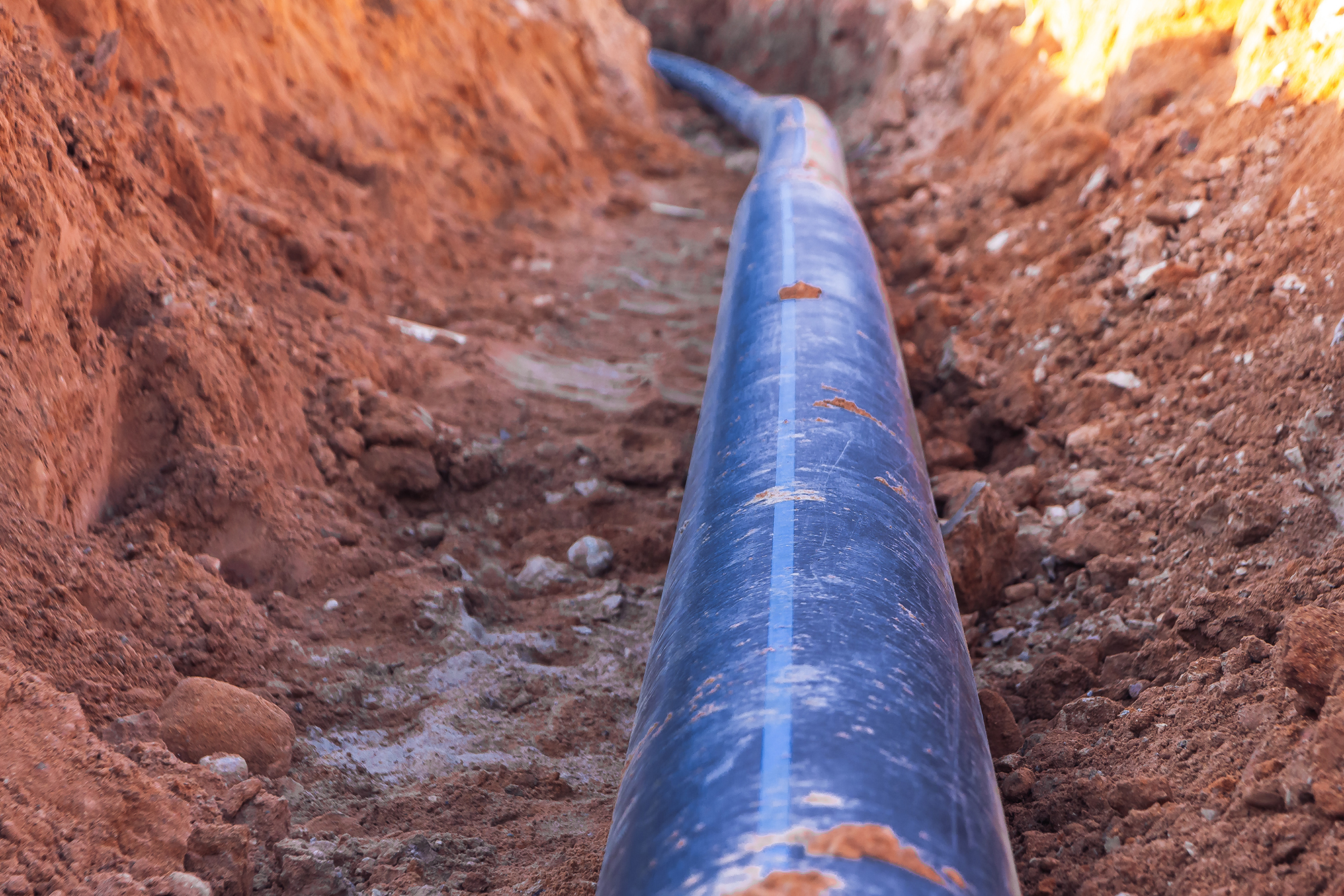 A black plastic pipe with a blue stripe lies in a dug trench to supply water to the house.